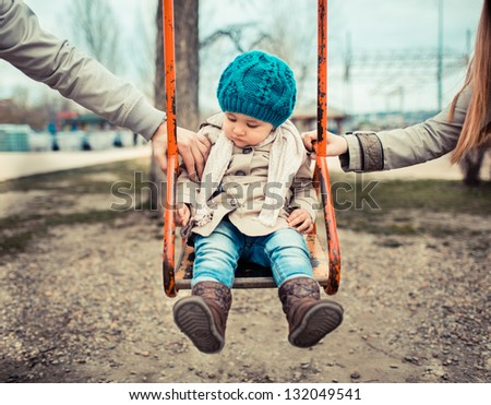 Sad Child On A Swing, In-Between Her Divorced Parents Holding Her Separately.