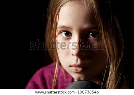 Sad child on black background. Portrait depression girl
