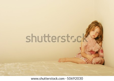 Sad child sitting alone on old mattress with a teddy bear