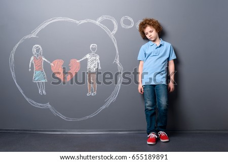 Sad child with broken heart. Boy is disappointed of parents' divorce, staying near a gray wall. #655189891