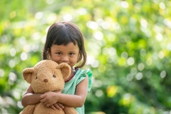 Sad child with Family problem, violence of parent is the one of divorce in bad relation family. Stress kid hugging teddy bear in park. Teddy Bear is a gift, toy, and best friend for children.