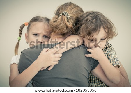 sad children hugging his mother