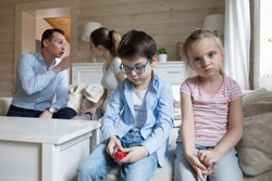 Sad children listen parents have angry fight at home. Stressed kids looking at camera, mom and dad shout. Violence, divorce, family problems, bad relationship negative impact on mental health concept