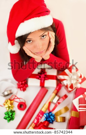 Sad christmas santa woman wrapping gifts depressed and bored wearing santa hat. Caucasian asian female model. - stock photo