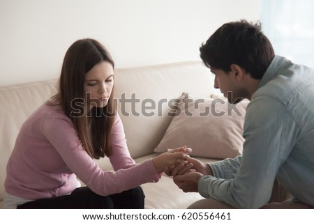 Sad couple sitting opposite one another, man holding hands of a woman. Loving husband comforting troubled young wife, compassionate boyfriend supporting crying girl, abortion or infertility problem