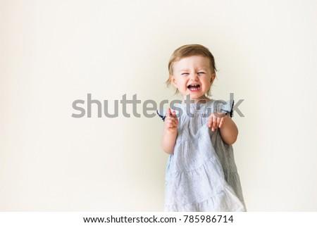 Stock Photo Sad crying emotional unhappy baby girl wearing dress isolated on white