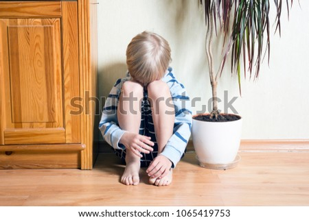 Sad cute little blonde boy sits on the floor and  looks directly
