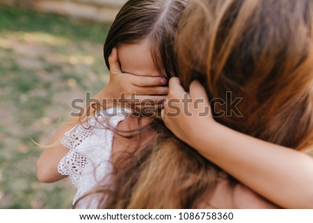 Sad dark-haired girl covers eyes with palm to wipe tears. Outdoor portrait of unhappy child with tanned skin crying and embracing mother's neck.