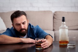Sad depressed addicted drunk guy having problem, suffer from alcohol addiction. Sorrowful young male with beard holds glass of whiskey at table with bottle of alcohol, in living room interior