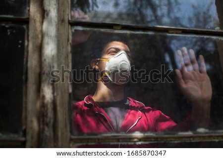 Sad depressed anxious young man wearing N95 protective medical mask looking through window,Coronavirus COVID-19 pandemic,self isolation&quarantine,social physical distance,stay at home safe,hope&faith