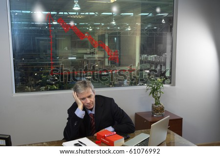 Sad depressed manager in his office with a chart showing loss
