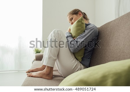 Sad depressed woman at home, she is sitting on the couch and hugging a pillow, loneliness and sadness concept