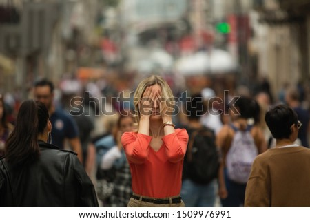 Sad depressed woman covers his eyes with his hands surrounded by people walking in crowded street. Panic attack in public place.  Stock photo ©