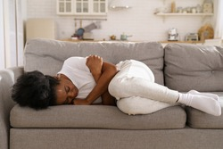 Sad depressed young African woman with crossed arms lying on couch at home crying, feeling loneliness, suffering from breakup. Upset Black girl has mental problems, can not forget her boyfriend.
