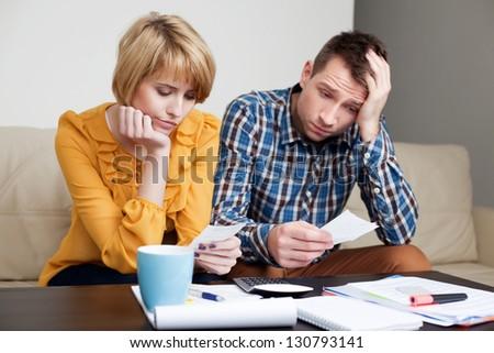 Sad, depressed young couple paying bills.