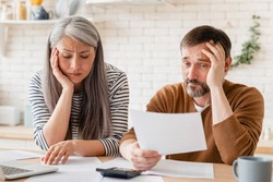 Sad disappointed mature middle-aged couple family wife and husband counting funds, savings, declarations, investments,paperwork, financial documents, bankruptcy, court case, bills, pension at home.