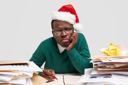 Sad dissatisfied man purses lips, keeps hand on cheek, wears Santa Claus hat, works hard before celebrating winter holidays, sits at desktop with pile of documets, writes information in organizer