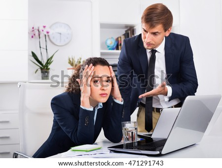 Sad dreary  subordinate woman being accused to making mistake by man colleague in company office