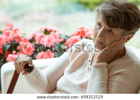 Sad elder lady sitting on the sofa and worrying about her health