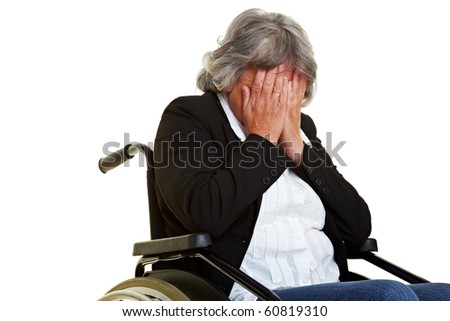 Sad elderly wheelchair user holding hands in front of her face