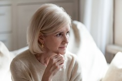 Sad elderly woman looking in distance thinking about life difficulties, thoughtful senior female feel lonely missing good old days, upset widowed wife grieve and sorrow for husband at home