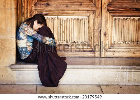 Sad elegant woman sitting and crying - stock photo
