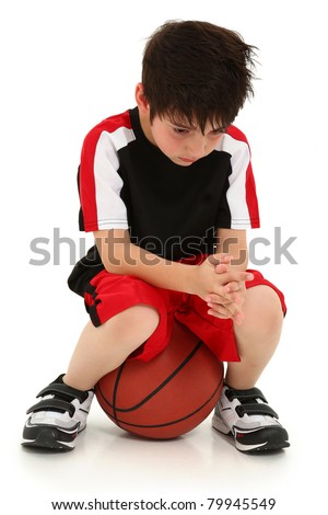 Sad elementary school boy sitting on basketball sad crying expression on face.