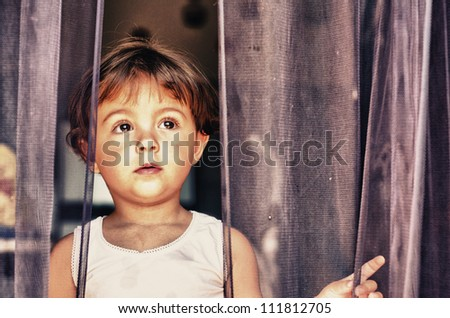 Sad face expression of Baby behind the Curtain - Italy