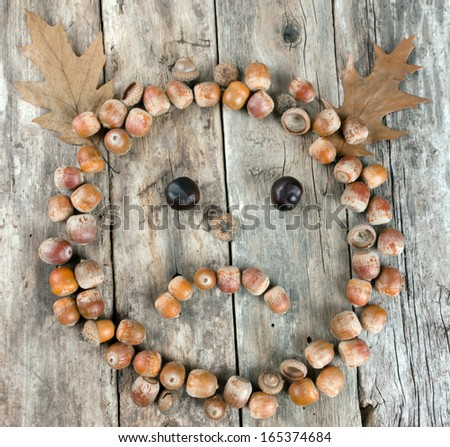 Sad face of acorns on a wooden background