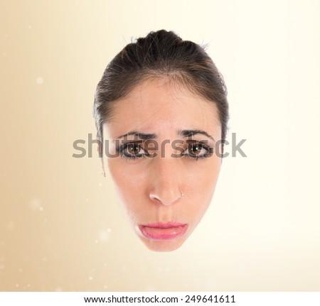 Sad face over ocher background