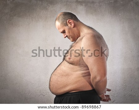 Sad fat man looking at his tummy - stock photo