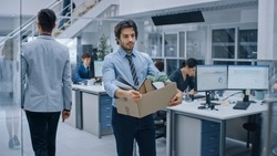 Sad Fired / Let Go Office Worker Packs His Belongings into Cardboard Box and Leaves Office. Workforce Reduction, Downsizing, Reorganization, Restructuring, Outsourcing. Shot with Dark Ambient