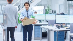 Sad Fired / Let Go Office Worker Packs His Belongings into Cardboard Box and Leaves Office. Workforce Reduction, Downsizing, Reorganization, Restructuring, Outsourcing. Mass Unemployment Market Crisis