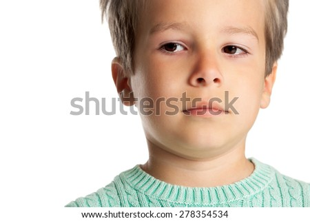 Sad five year old boy posing over white studio background. Closeup of child face in tears.