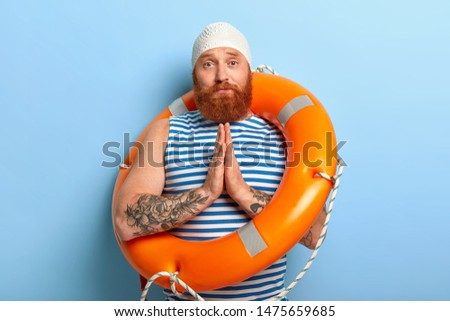 Sad foxy male asks swimming instructor for help, wants to learn swim, presses palms together in praying gesture, stands with orange lifebuoy, casually dressed, spends summer vacation at seaside
