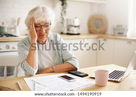 Sad frustrated senior woman pensioner having depressed look, holding hand on her face, calculating family budget, sitting at kitchen counter with laptop, papers, coffee, calculator and cell phone