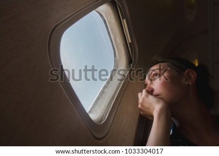 Sad girl at the porthole in the plane. Young woman on passenger seat near window in airplane
