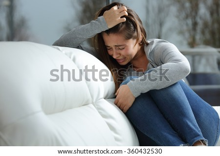 Sad girl crying desperately alone sitting on a couch at home in a dark winter day