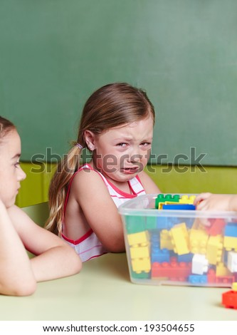 Sad girl crying in a kindergarten group
