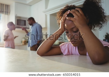 Sad girl listening to her parents arguing in kitchen at home #650314015