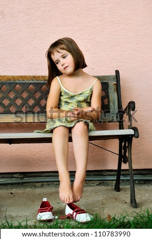 Sad girl - outdoor portrait of small cute child sitting on bench