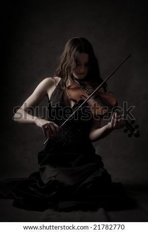 sad girl play on violin in dark room