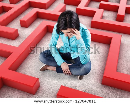 Sad girl sits in a labyrinth with red walls