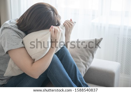 Sad girl sitting on couch and hugging a pillow, loneliness and sadness concept