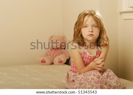 Sad girl sitting on old mattress