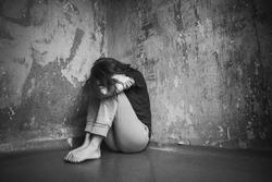 Sad girl sitting on the floor in corner of room