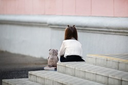 Sad girl with a plush toy sits on the steps of the school stairs with her back to the camera. Offended child. Selective focus.