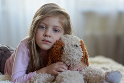 Sad girl with a toy dog on the bed