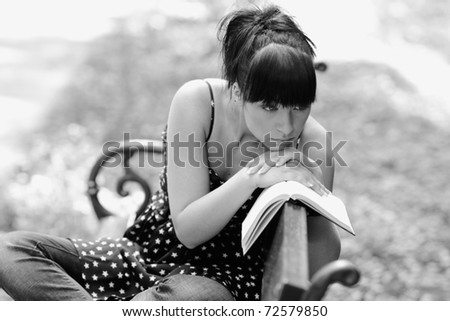 sad girl with book sitting on the bench