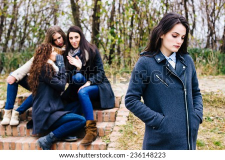 Sad girl with friends gossiping in background,  behind her back ストックフォト ©